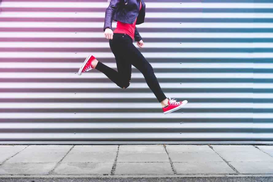 young-happy-woman-jumping-in-front-of-metal-wall-picjumbo-com